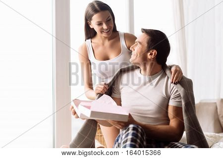 I love my girlfriend. Handsome happy positive man holding an empty gift box and looking at his girlfriend while enjoying her care about him