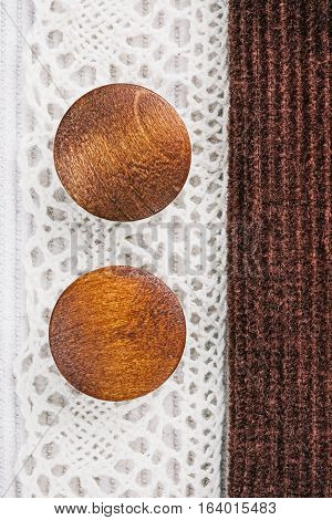 Milky white and chocolate brown corduroy combination with cotton lace and wood buttons. Macro view