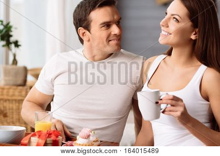 Having breakfast together. Joyful nice pleasant woman smiling and holding a cup of tea while having breakfast with her boyfriend