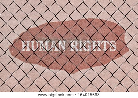 Text Human Rights written under a wire fence