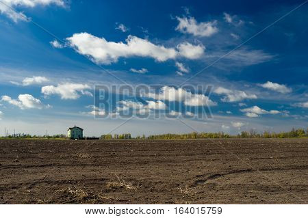 Autumnal country landscape with low skies under lonely house.