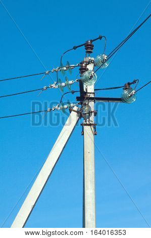 Concret prop of power supply line with wires over clear cloudless blue sky