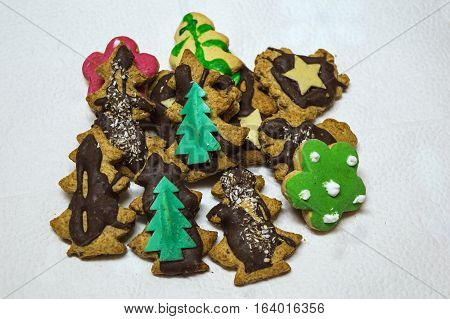 Close-up Christmas Cookies on a White Background. Christmas decoration. Christmas gingerbread men tree with chocolate glaze green flower star with chocolate glaze.