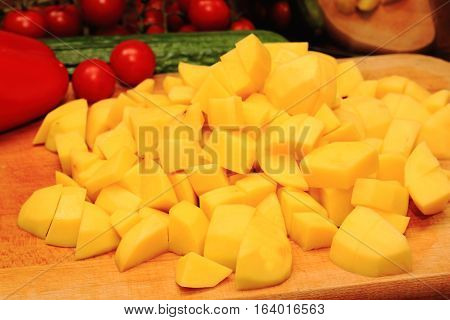 Sliced potatoes and vegetables on wooden cutting board