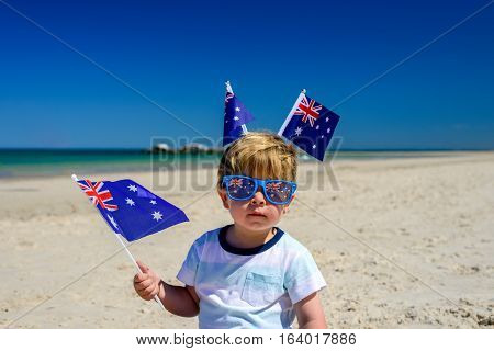 Cute smiling kid with Australian flags sitting on the sand at the beach on Australia Day