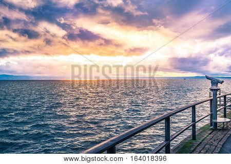 Binocular on a lake shore at sunset - Landscape with a colorful sunset over the Bodensee lake and its shore equipped with tourists binoculars and metal railing for safety.