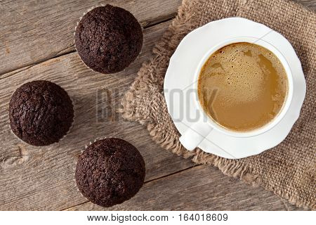 Chocolate cupcakes and white cup of cappuchino