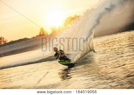 Waterskier moving fast in splashes of water at sunset. Man wakeboarding on a lake