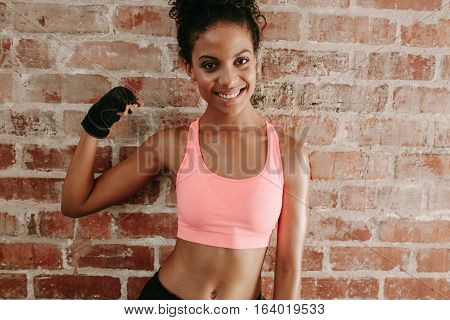 Portrait of young fitness woman flexing muscles and smiling against brick wall. African female model in sportswear showing her muscles n gym.