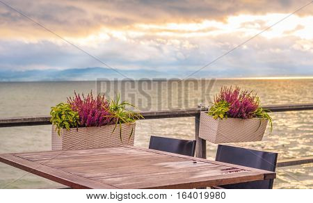 Outdoor table on lake shore - Conceptual image with an empty table on a terrace on the shore of the Bodensee lake at sunset.