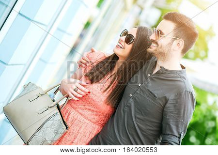 Couple of tourists walking in a city street and shopping together.