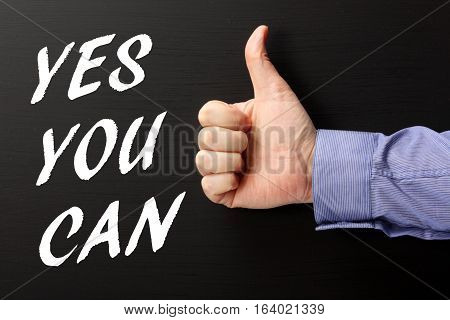 Male hand in a business shirt giving the thumbs up sign to the words Yes You Can in white text on a blackboard