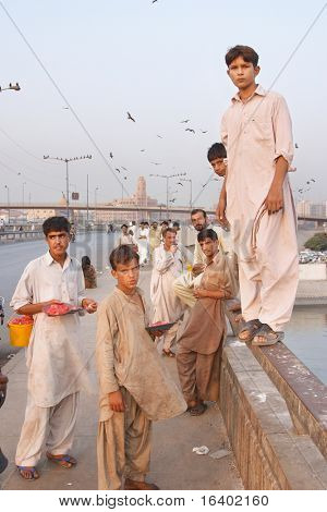 KARACHI, PAKISTAN - NOV 14: Boys on the Netty Jetty Bridge sell offal for kite feeding on November 14, 2006 in Karachi, Pakistan. Kite feeding is a favorite activity for local people