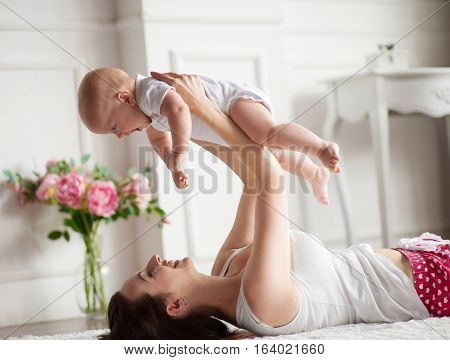 Young mother playing with her baby. She throws up him and they are gaily laughing .