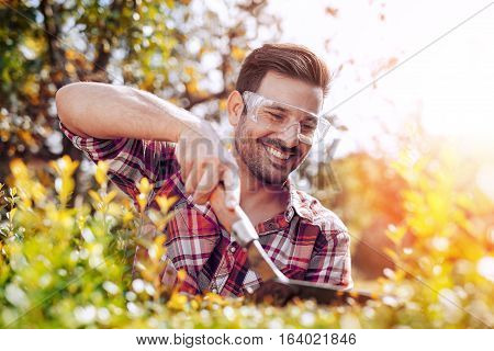 Portrait of a professional gardener.Young man working in garden.