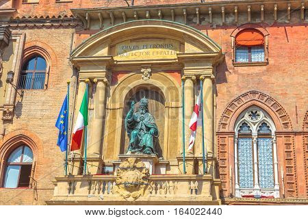 Close up of bronze statue of Pope Gregory XIII on Palace of Accursio or Comunale facade, overlooking Piazza Maggiore in Bologna, Italy.