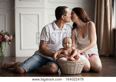 Happy young parents close to small baby in wicker basket. Parents kissing and hugging their child.