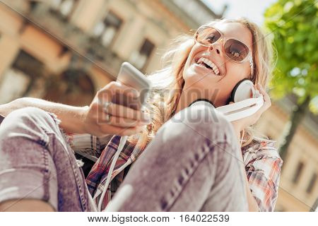Young woman listening to music on a smart phone.She is listening music on smart phone in the city.
