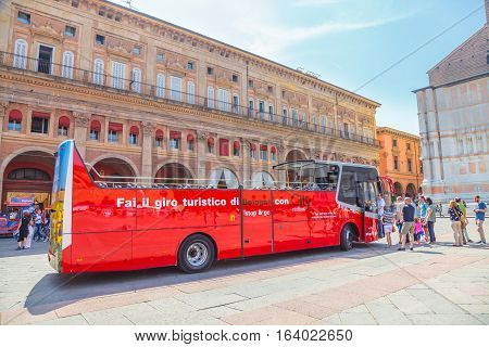 Bologna, Italy - May 28, 2016: perspective view of City Red Bus, the tourist bus service to explore Bologna city, in front of Palazzo dei Banchi in Piazza Maggiore or main square.