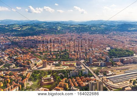 Aerial view of Bologna city in Italy with Asinelli Towers, San Luca Basilica church on Bologna hill and train station.