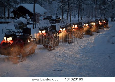 line up of switched on snowmobiles ready for an excursion