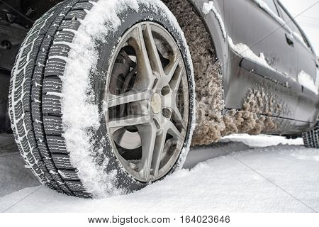Detail of car. Tire standing on winter road with deep snow