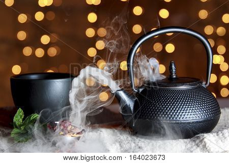 Smoking hot tea in black ceramic pot with black cup and Christmas lights