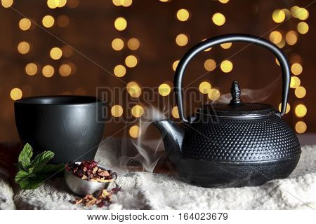 Smoking hot tea in black ceramic pot with black cup with Christmas lights