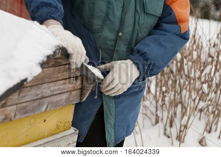 Beekeeper removing snow from a beehive horizontal outdoor shot with particular focus