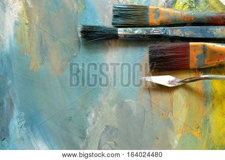 Artist paint brushes and oil paints on wooden palette. Mixed oil paints in different colors. Palette with paintbrush and palette-knife.