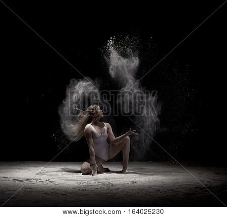 Female sexy gymnast with her blonde hair loose in beige bodysuit sitting gracefully on her knee black background with white dust all over body shot made in profile.