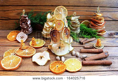 Winter decorations with dried fruit and citrus, thuja and candles on the wooden background