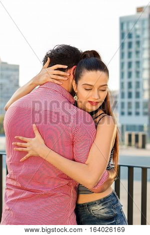 Young woman hugs man. Two people on city background. Feelings get stronger every day.