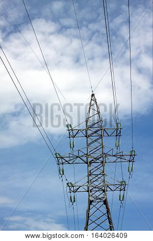 High-voltage power line metal prop with wires over cloudy blue sky vertical view
