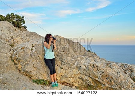 Girl tourist photographing the landscape at sunset. Sudak. Crimea