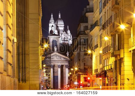 Night view of Sacre-Coeur Basilica or Basilica of the Sacred Heart of Jesus and Notre-Dame de Lorette church, seen from Rue Laffitte, Paris, France
