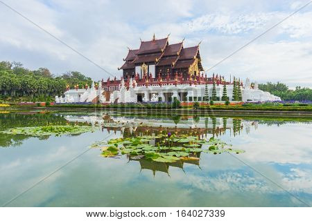 Traditional thai architecture in the Lanna style Royal Pavilion (Ho Kham Luang) at Royal Flora Expo Chiang Mai Thailand in morning mist with blue sky and clouds.