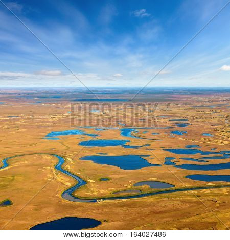 Aerial view of the tundra in autumn. Marsh with water under cloudy sky.