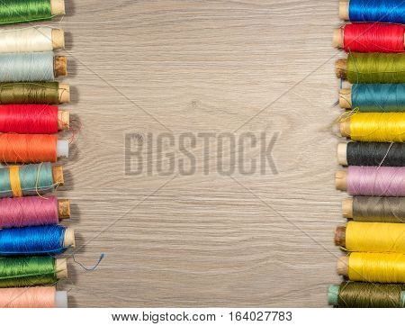 Sewing tools and accessories on wood background. Sewing threads on bobbins.