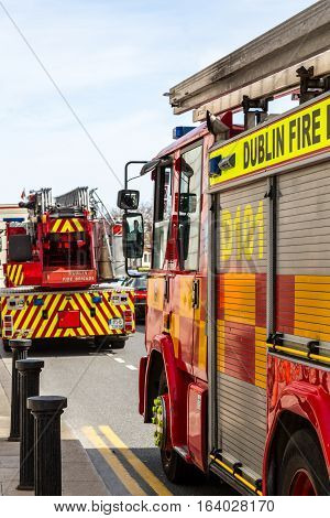 Two fire engines on city street. Dublin, Ireland - April 21, 2016: Two fire engines from Dublin fire Brigade on a street in Dublin during emergency rescue. Dublin fire Brigade engines on street.
