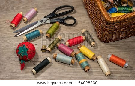 Sewing tools and accessories on wood background. Sewing kit. Thread on bobbins, scissors, needles, thimble and sewing box.