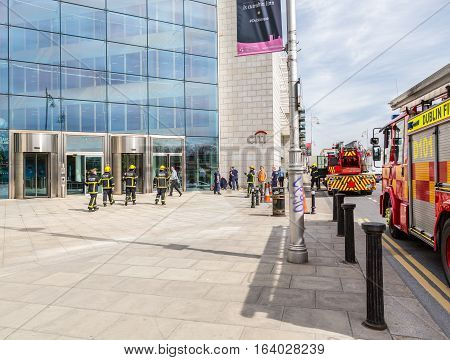 Firefighters outside a building. Dublin, Ireland - April 21, 2016: Two fire engines and a group of firefighters from Dublin Fire Brigade outside a building.  Firefighters talking. People passing by.
