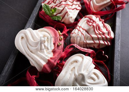Homemade meringues in heart shape in old wooden box for Valentine's day.