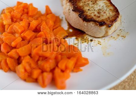steamed carrots with roasted pork chop served on white plate
