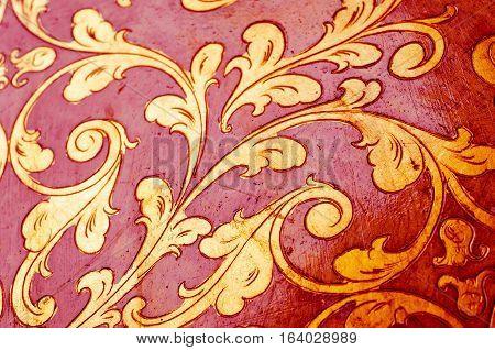 Fourish pattern. Gold leaf floral design on red background. Old antique surface.