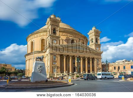 Mosta Malta - The Church of the Assumption of Our Lady commonly known as the Rotunda of Mosta or Mosta Dome at daylight with moving clouds and blue sky