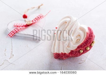 Homemade meringues in heart shape on light stone background. Valentines day concept, copy space.