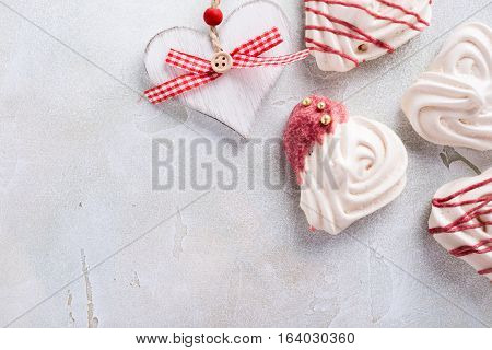 Homemade meringues in heart shape on light stone background. Valentines day concept, top view, copy space.