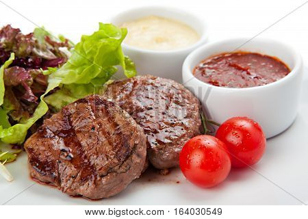 Barbecue grilled beef steak meat with vegetables and sauses.