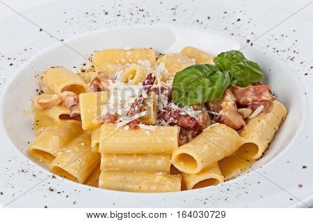 Close-up of italian rigatoni pasta with prosciutto parmesan cheese and leaf basil.